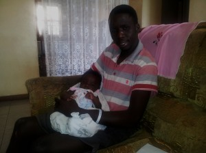 My friend Collins holding his baby nephew while we waited for dinner at his parents house.