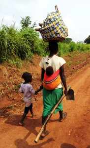 Women in Uganda know how to carrying multiple items.  You can't see the water jug on her head in this picture!