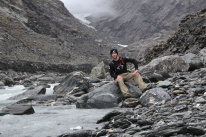 Me sitting next to a stream with Franz Josef Glacier in the background